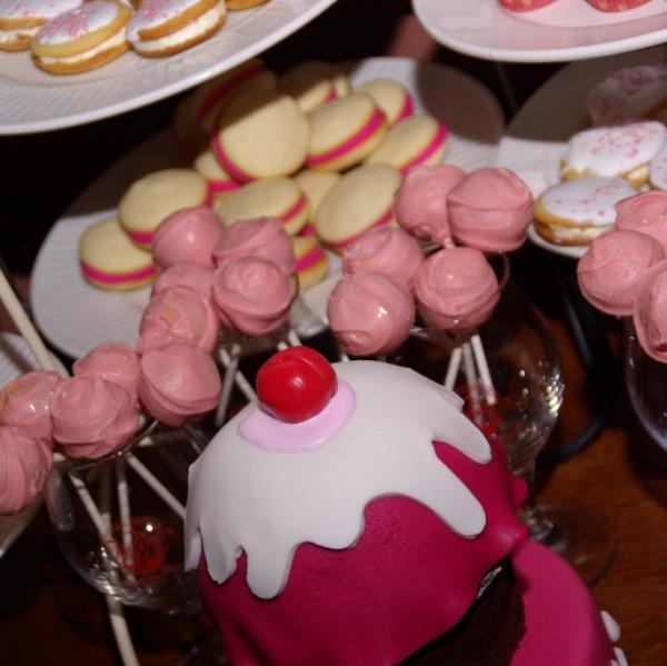 baklava cakepops en whoopie pies met roze marsepeinvulling op de voorgrond: aansnijtaartje van chocolatemudcake in de vorm van een cupcake