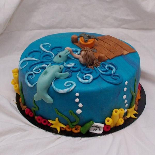 taart met dolfijnen en zwemmend meisje zwemmen met dolfijnen