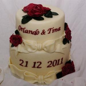 ivoorkleurige bruidstaart met strikken en donkerrode rozen rotterdam nesselande TAART & kUNST