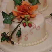 bruidstaart met gumpaste herfst bloemwerk en bijpassende minitaartjes