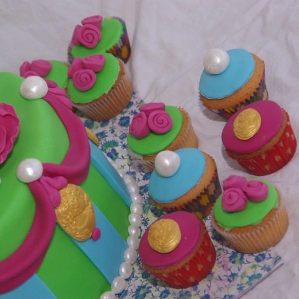 vrolijke groen blauw roze taart met bijpassende cupcakes