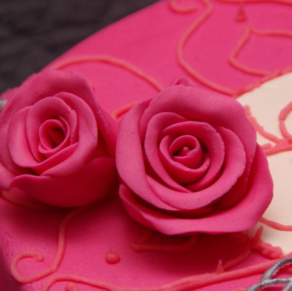 roze roosjes op roze chocolade taart